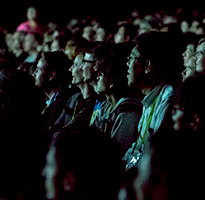 Smiling SIGGRAPH attendees in a theater.