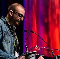 SIGGRAPH presenter speaks at a session podium.