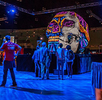 SIGGRAPH attendees observe an oversize, pink, blue, and orange patterned skull.