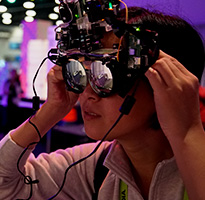 SIGGRAPH attendee trying on a headset with mirrored lenses.