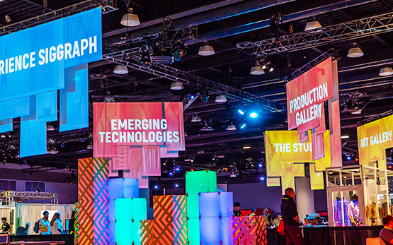 """Experience SIGGRAPH,"" ""Emerging Technologies,"" ""Production Gallery,"" ""The Studio,"" and ""Art Gallery"" banners hanging from the ceiling."