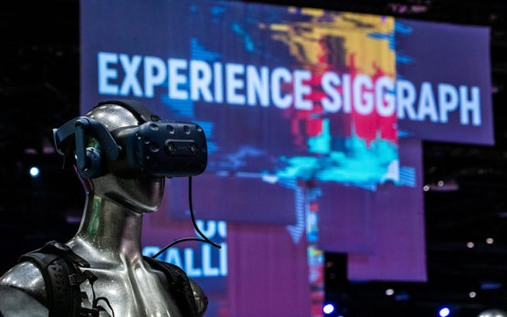 Mannequin wearing a VR headset in the foreground with an Experience SIGGRAPH sign in the background.