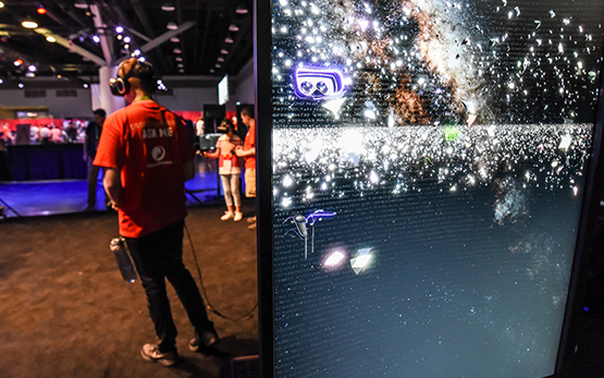 A SIGGRAPH volunteer wears a headset, through which he views a dark background filled with star-like sparkles.