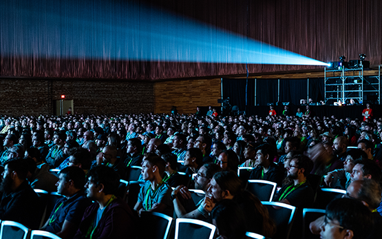 SIGGRAPH attendees sit in a theater, facing a screen, and a projector shines from the back.