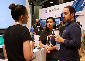 Three SIGGRAPH attendees in conversation at the Google Cloud exhibit booth.