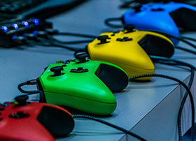 Red, green, yellow, and blue game controllers sitting on a counter top.