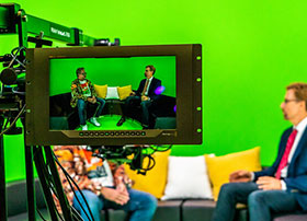 Two SIGGRAPH attendees on camera in a green room.